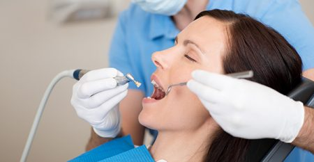 21246825 – mature dentist examining female patients mouth in clinic